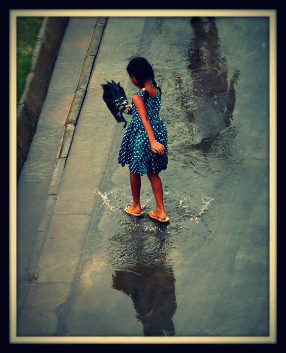 A girl and her shadow in the rain water.